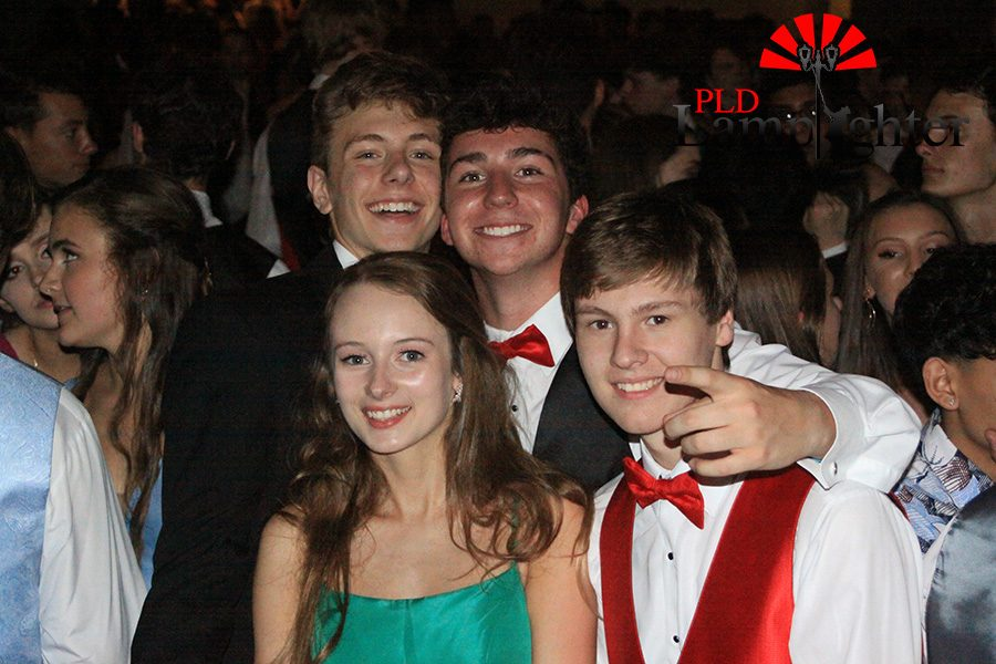 A group of friends pose for a picture while enjoying themselves at prom.