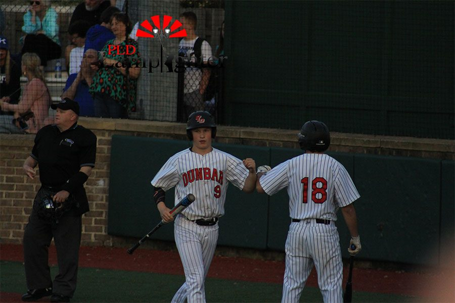 #9 Gunnar Wheatley bumping #18 Cameron Baughman's arm on the way to the dugout.