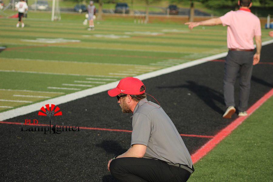 Dunbar coach kneeling down to watch his team.