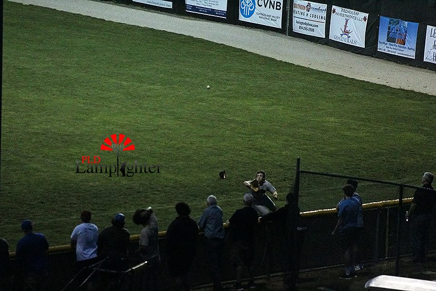 A PLD player goes deep into the foul to catch a foul ball.