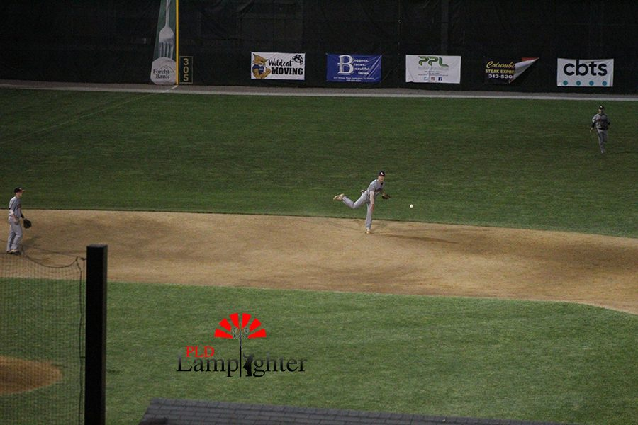 A PLD player makes a long through to first base.