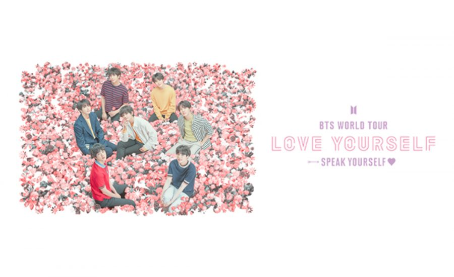 KPOP sensations BTS sit amongst a field of flowers next to the tour title