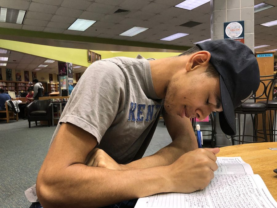 Darius Derden preparing for AP exams by taking a practice test in Dunbar's Library.