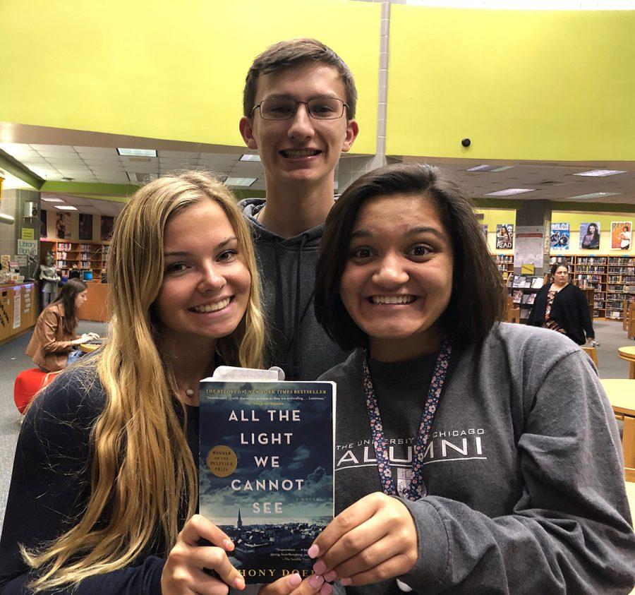Three Dunbar sophomores holding book number three on Teagan's list.