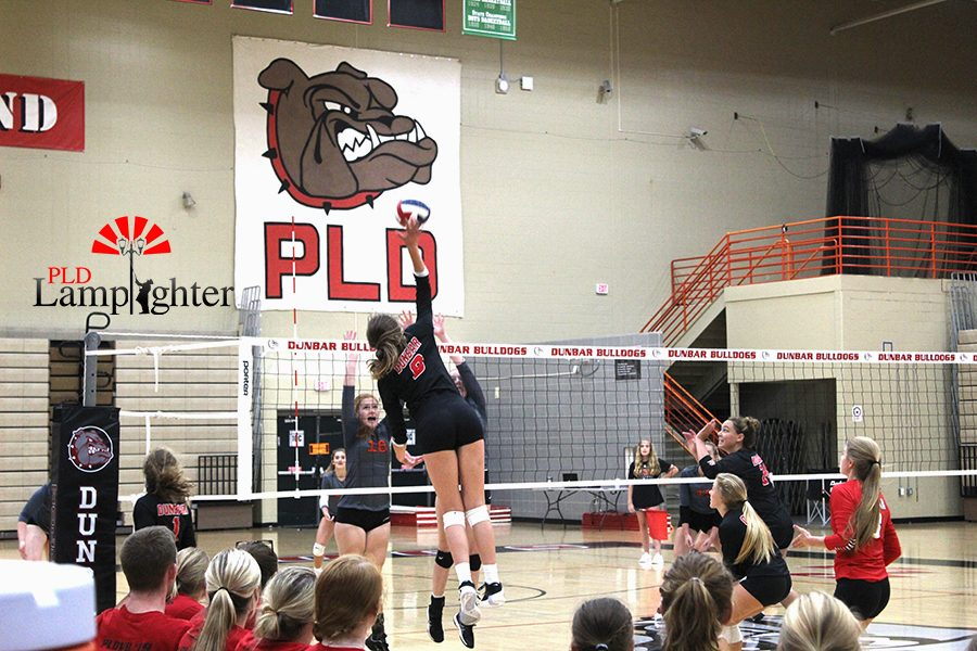 #8 Olivia Stots, jumps up to make an attack on the volleyball while the opponents try to block the shot.