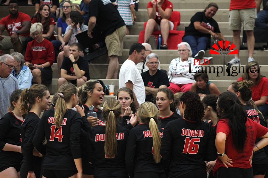 The volleyball team huddles up to talk strategy during a time out.