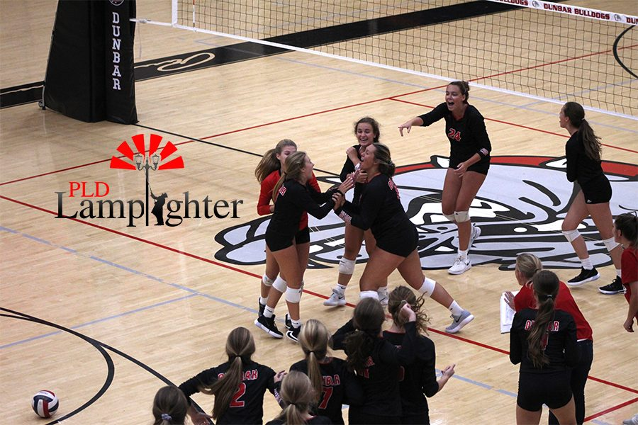 The volleyball players celebrate a score.