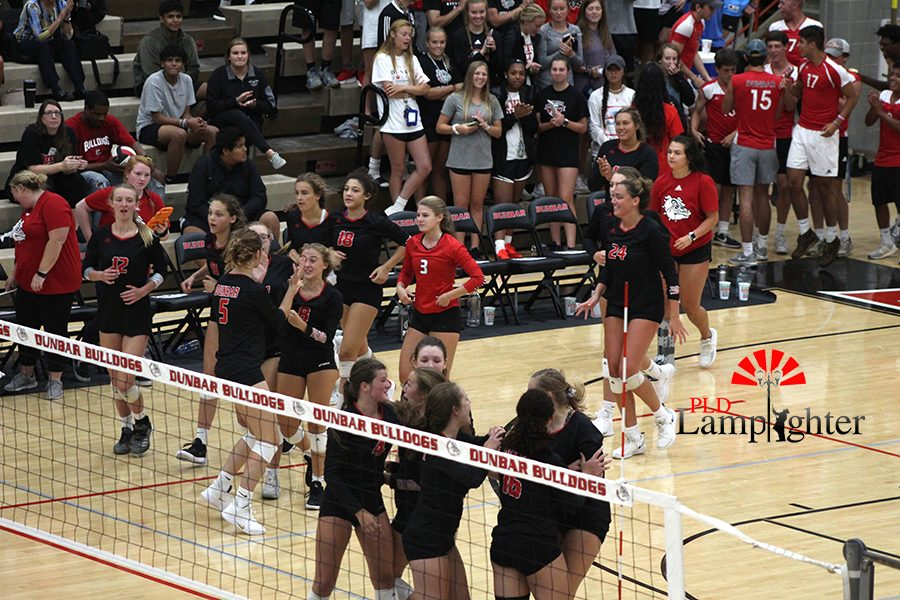 The volleyball team come together to celebrate their victory.