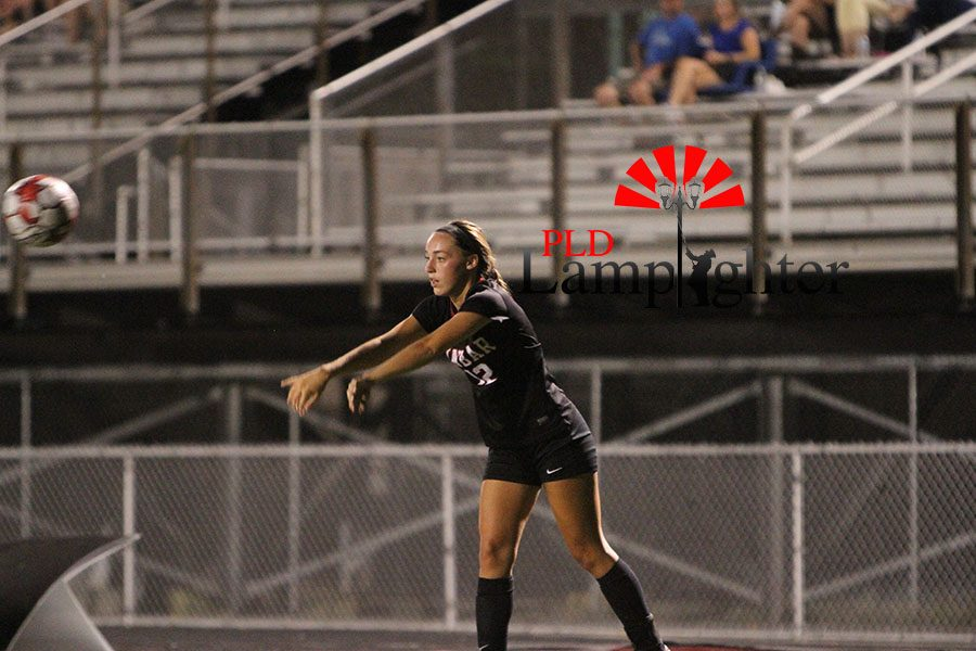 #12 Carmen Combs throws the ball back in play.