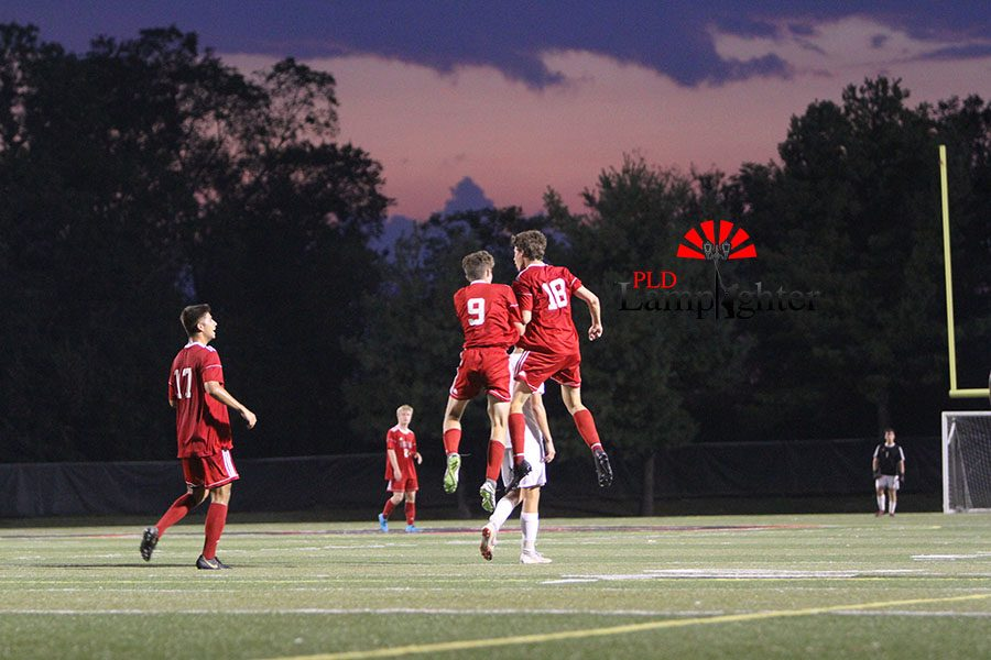 #9 Ben Oser and #18 Jed French celebrate after a Dunbar goal.