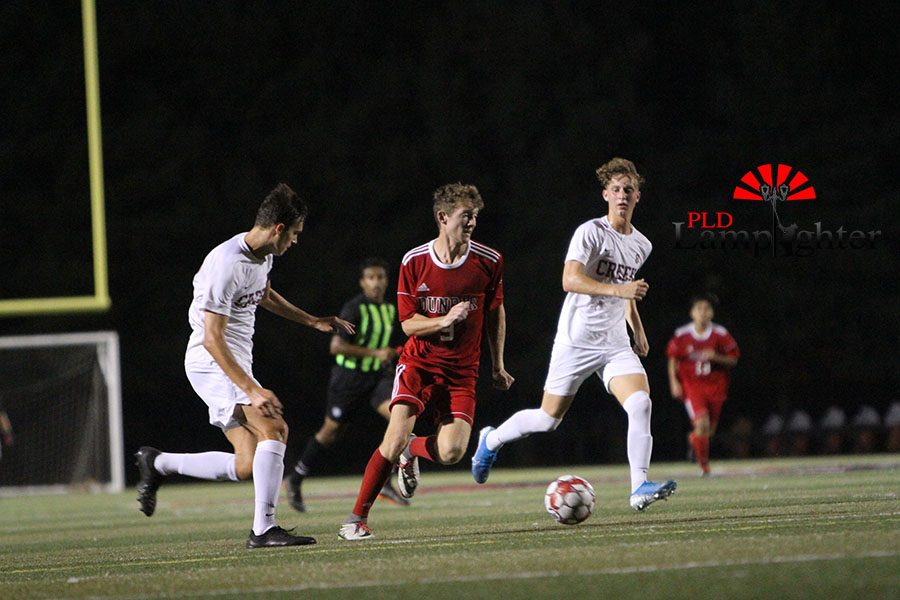 #9 Ben Oser races past two Tates Creek defenders towards the goal.