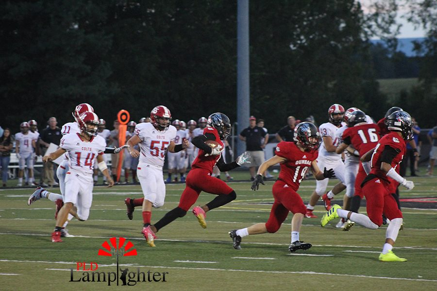 #1 Mitchell Joseph runs the ball to gain yardage before being tackled down.