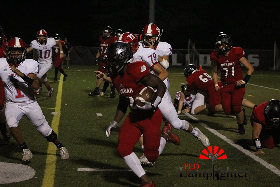 #2 Mitchell Joseph, attempts to run the ball to gain yardage before getting tackled.