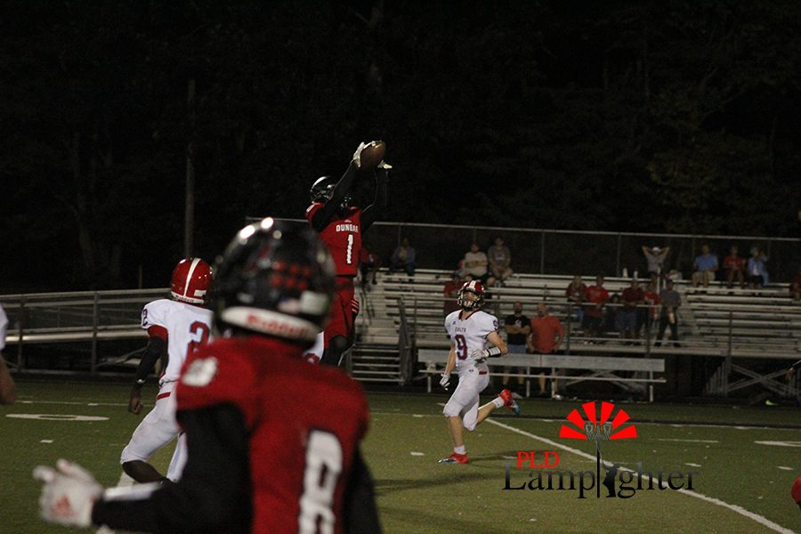 #1 Jamarcus Robinson, leaps into the air to receive the ball.