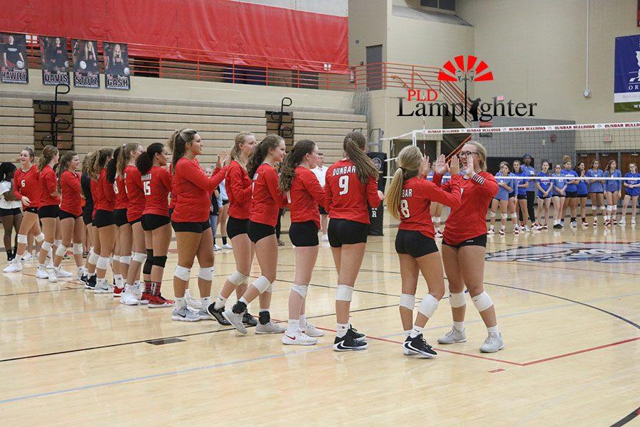 Dunbar volleyball team high-five as their names are announced.