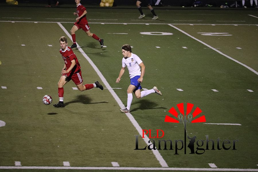#12 Derek Burgess hurries to protect the ball from the Newport Central Catholic Thoroughbreds.