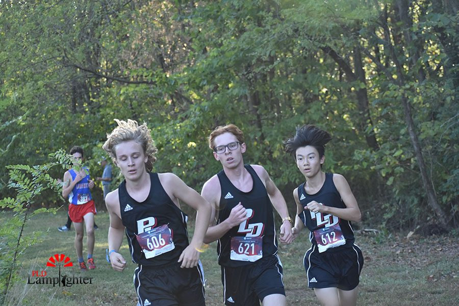 Abram Cavins, who finished with a time of 20:38.26, Ethan Sanning, who finished with a time of 20:39.12, and Rinta Kubo making the turn at the second viewing area.