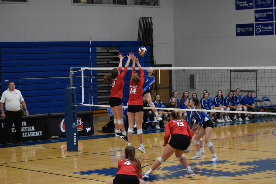 Dunbar volleyball players spike the ball over the net to the other team.