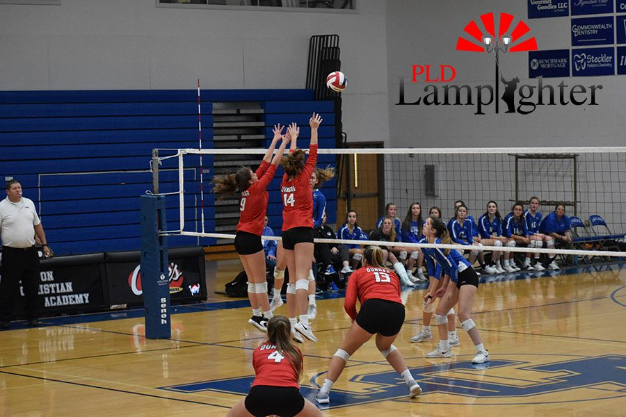 #9, Ava Jackson, and #14, Eleanor Davis block the ball