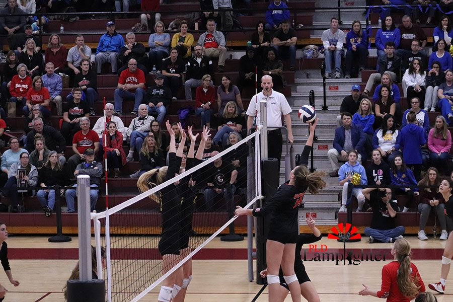 #14 Eleanor Davis hitting the ball over some Henry Clay players