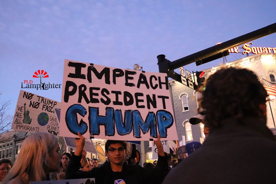 A man holding a sign present at the climax of the protest using a play on the president's name.
