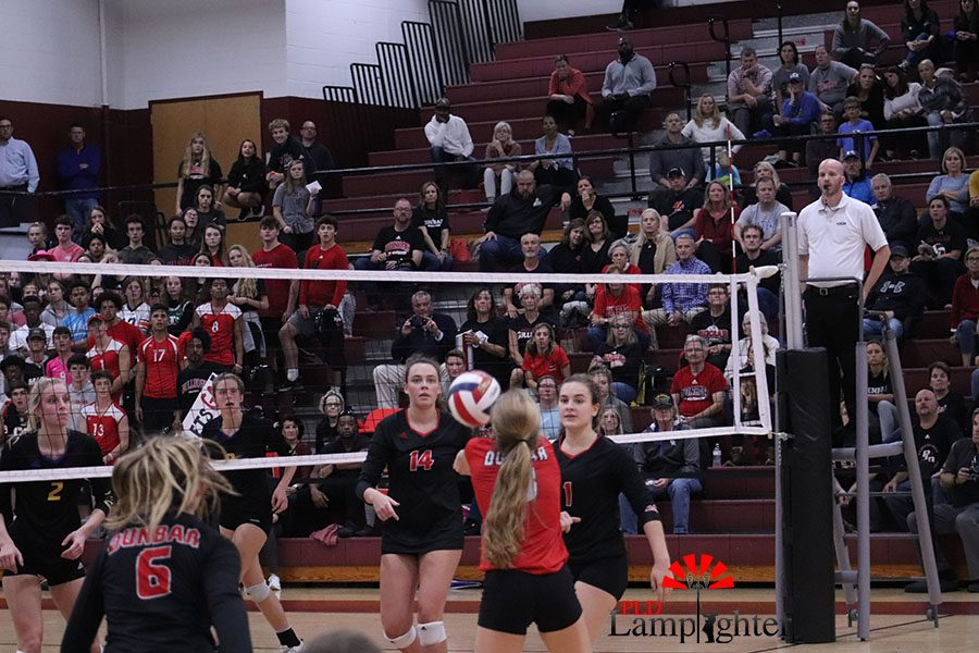 #3 Caroline Cole hitting the ball up into the area to set up another player for a set