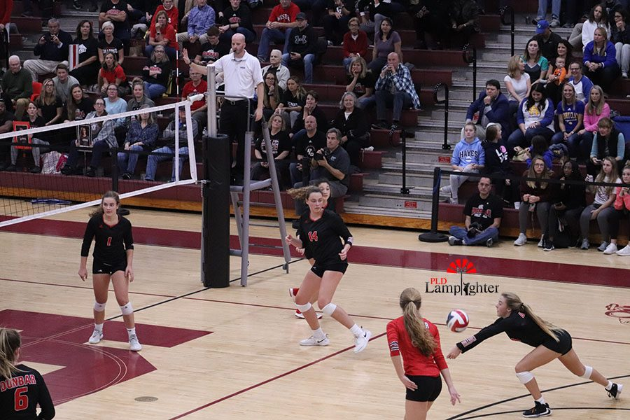 #8 Olivia Stotz diving out to save the ball from hitting the ground and keep the serve alive