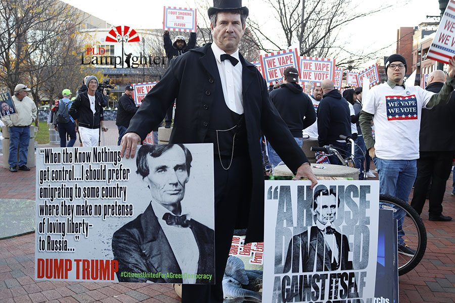 A man posing as Abraham Lincoln displaying signs with some of Lincoln's more famous quotes on them with a small group of protesters behind him.