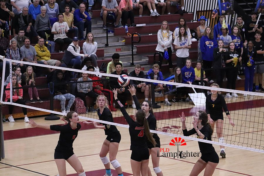 #4 Campbell Gash setting up #5 Marguerite Jouet for a spike with Henry Clay players preparing to block it