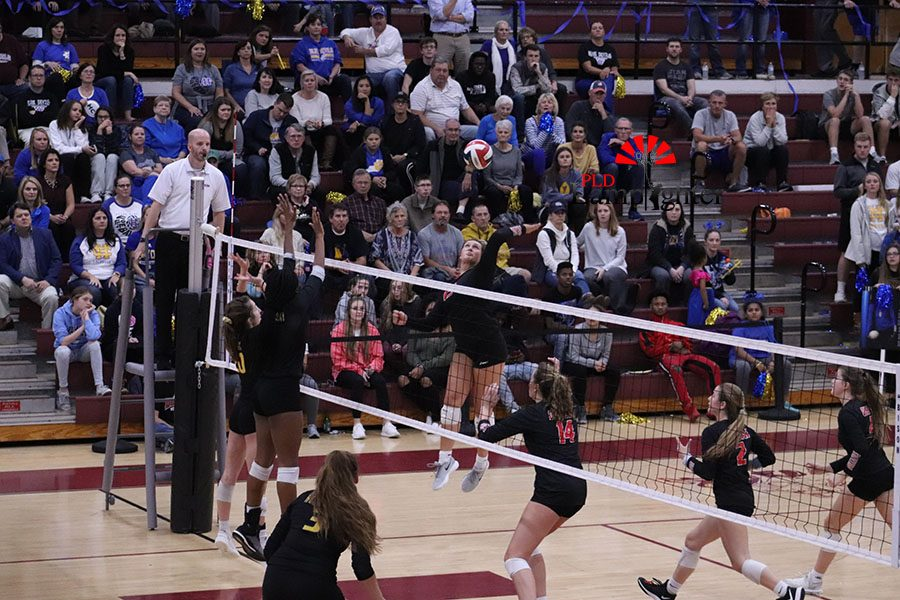 #13 Peyton Gash rising to spike the ball trough 2 Henry Clay players