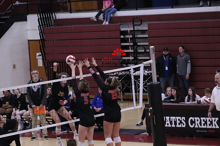 #5 Marguerite Jouet and #13 Peyton Gash rising to block a hit by a Henry Clay player that would roll off the finger tips of #5 Jouet