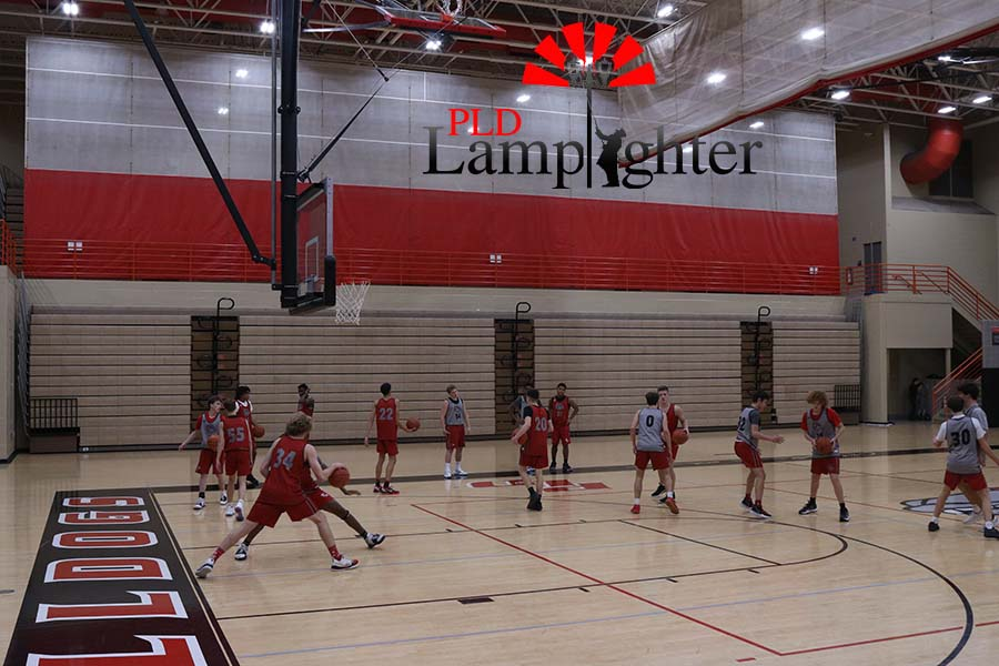 The boys basketball team practicing defense.
