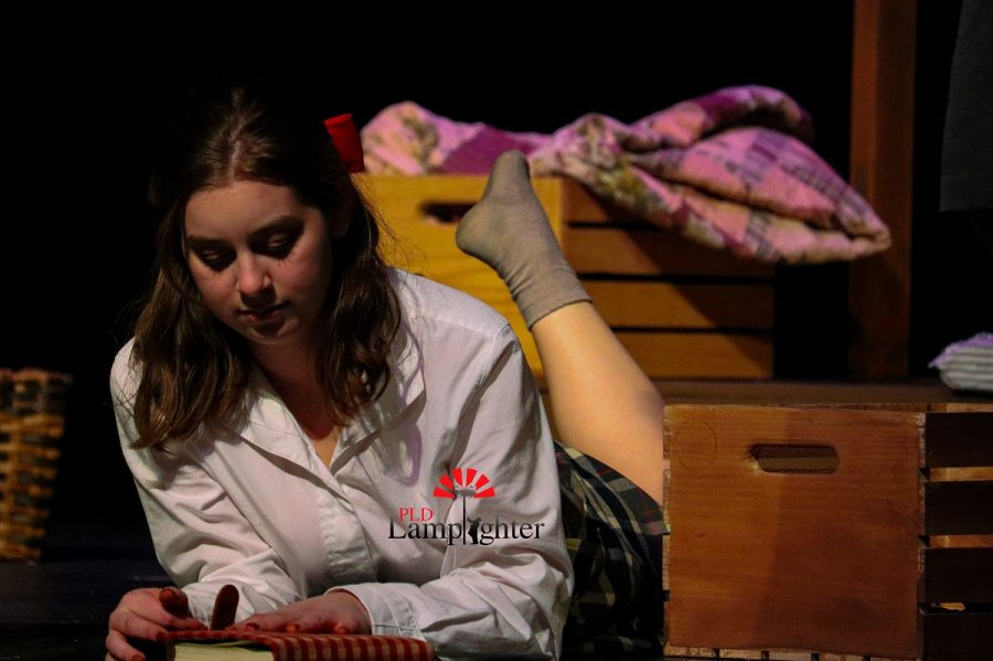 Anne (Jaycee Castro) lays on the floor and writes in her diary. Annes diary is now famous for giving firsthand experience as to what it was like to live during the war and in hiding.