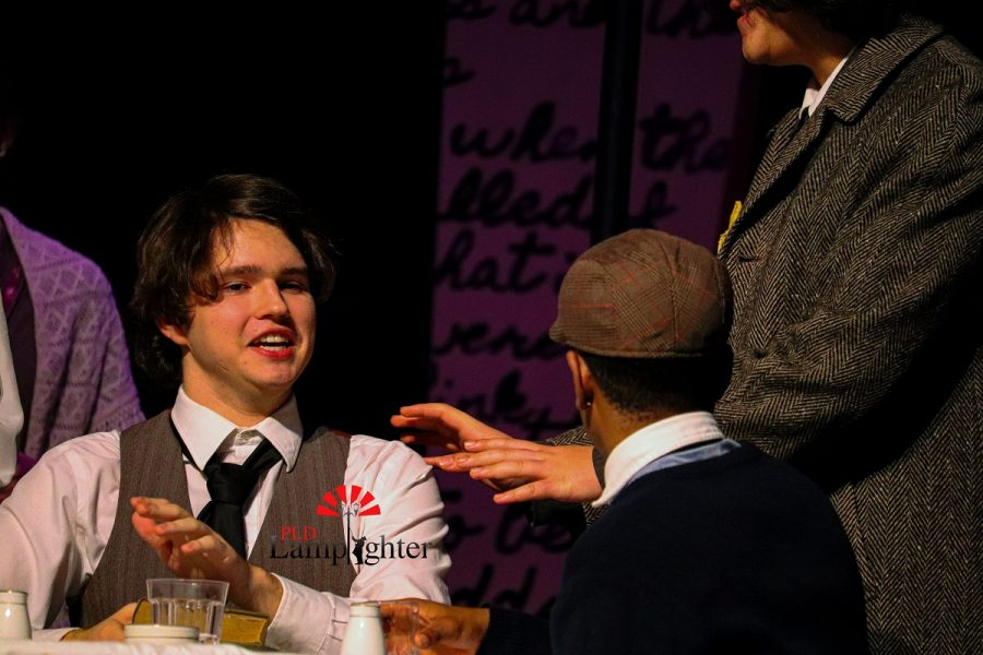 Mr. Frank (George Gordan) and Mr. Van Daan (Yousuf Alazawi) are talking about whether or not Mr. Frank should help Peter (Esoso Kaumba) with his studies.