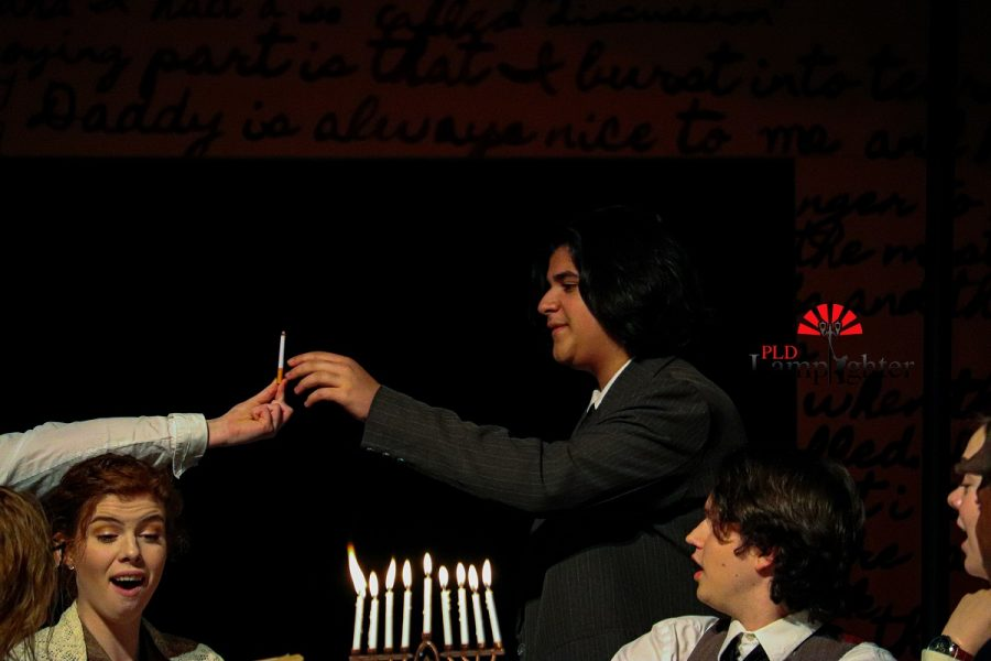 Anne (Jaycee Castro) holds out a cigarette for Mr. Van Daan (Yousuf Alazawi) as a present she made for Hanukkah as everyone around the table watches.