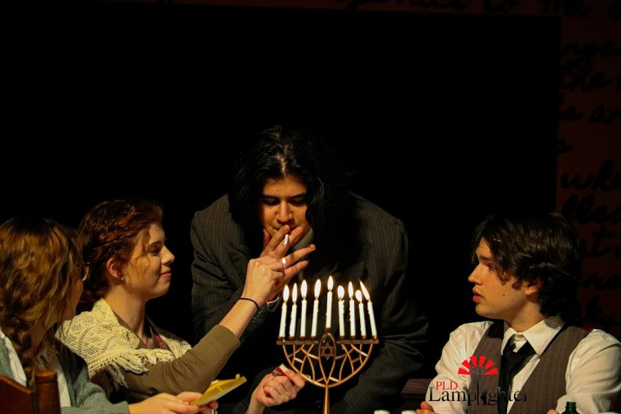 During Hanukkah, Anne makes presents for all the residents from whatever she can find. Mr. Van Daan (Yousuf Alazawi) is holding out the cigarette that Anne made for him as Mrs. Frank (Kylie Schmidt) lights a match for him.