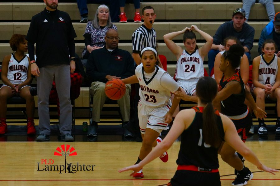Tanaya Cecil (#23) dribbles past to look for a teammate to pass to.