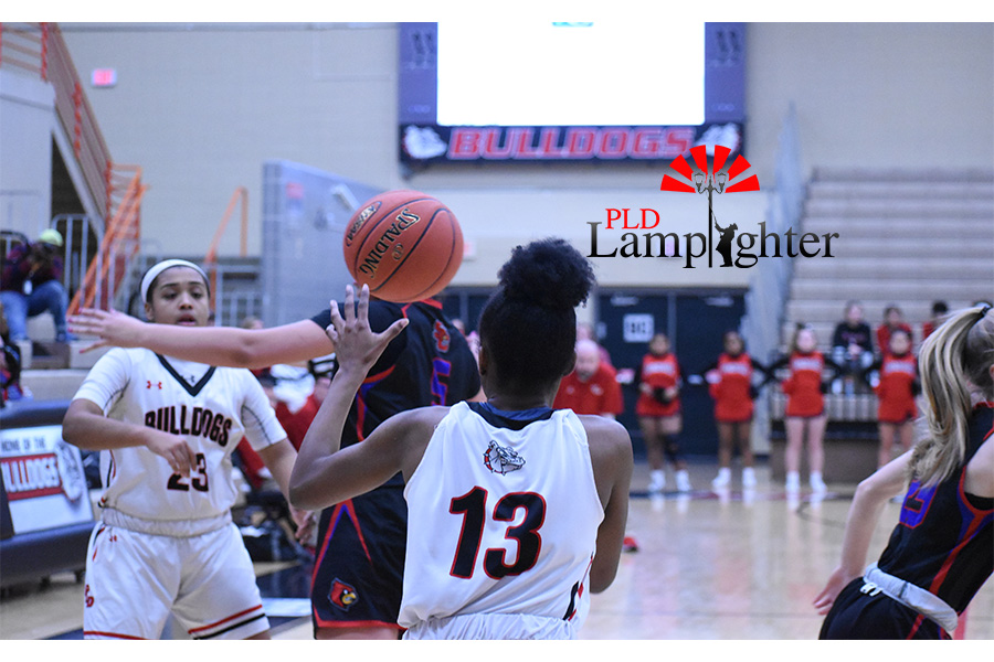Tanaya Cecil (#23) passes the ball to teammate, Aziah Campbell (#13), to get points.