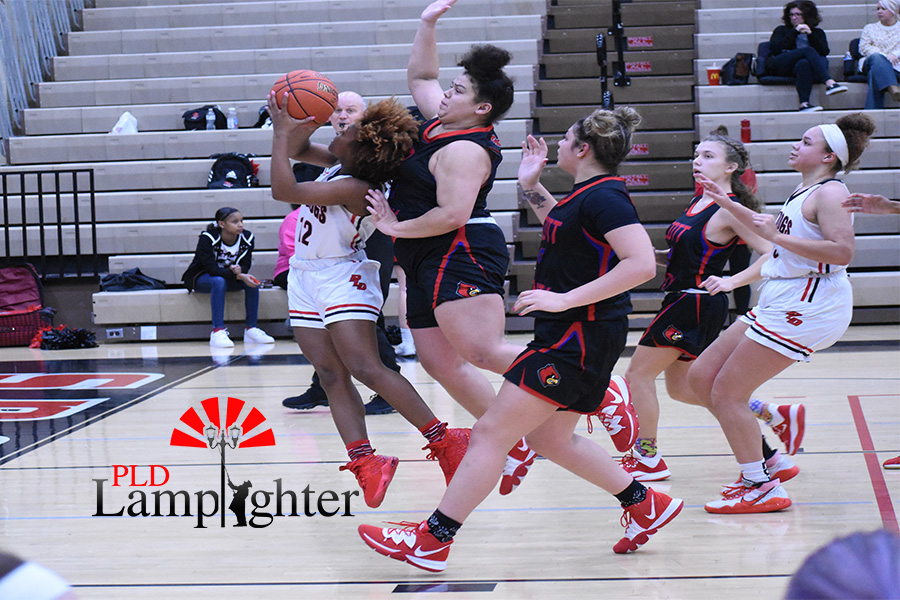 DelTarria Jackson (#12) goes in for a layup while getting pushed from behind.