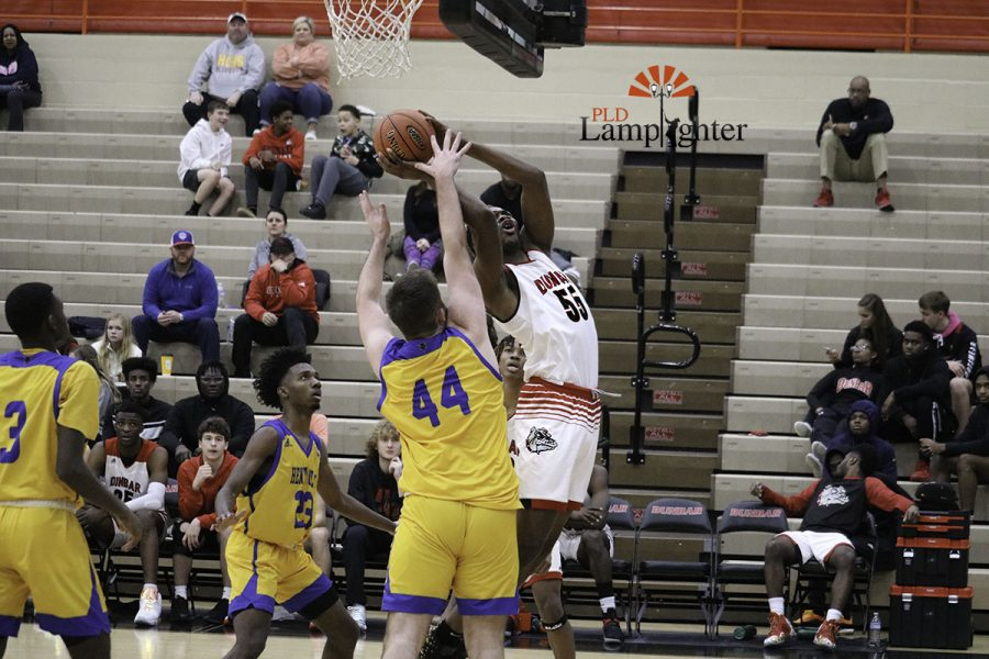 Number 55 going in for layup against big defender number 44.