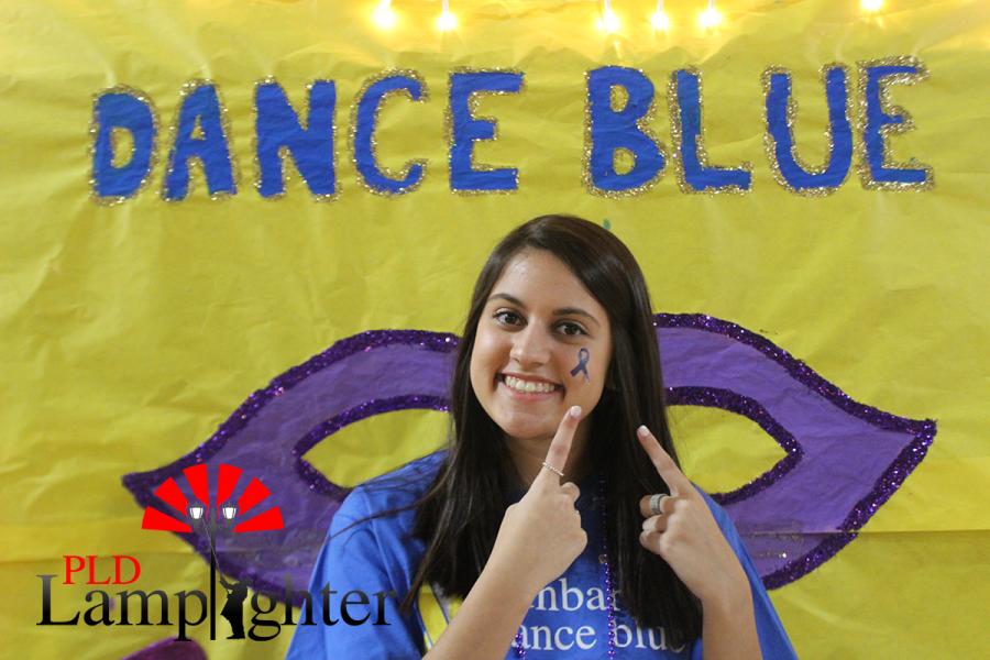 Samira Kiessling showing off her Dance Blue tattoo in front of a Mardi Gras backdrop.