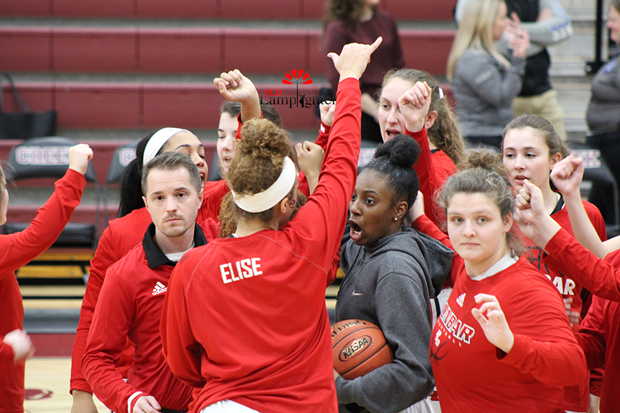 The girls' basketball team does their team chant before tipoff.