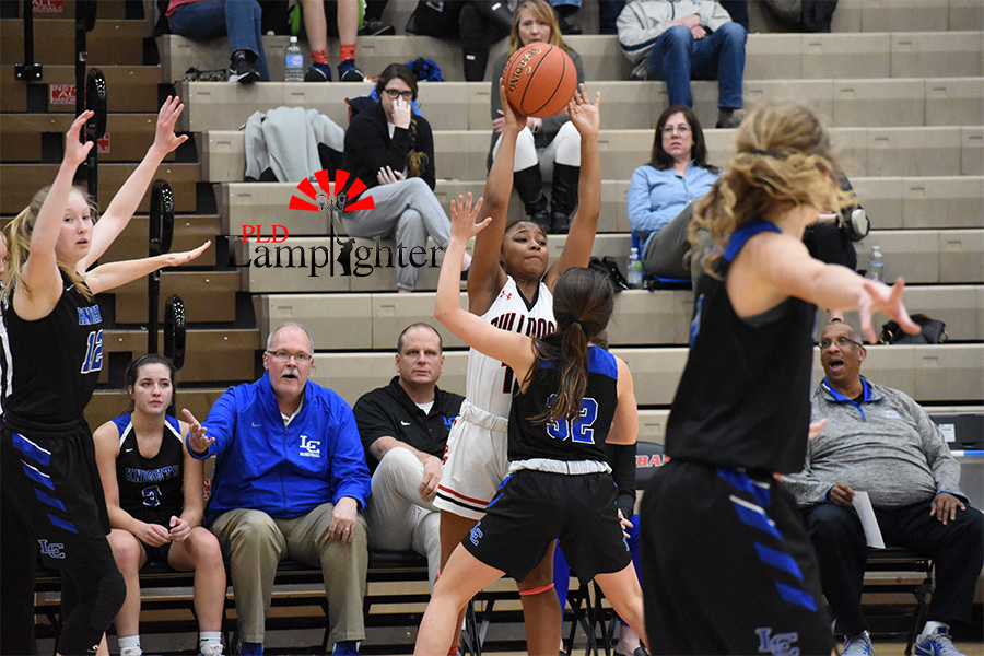 #12 reaches to pass the ball to one of her teammates.
