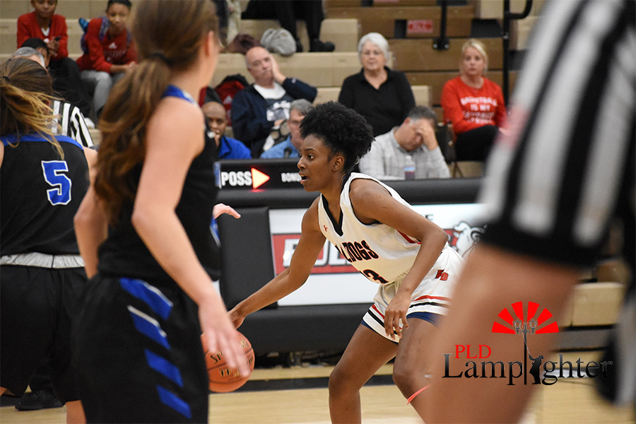 Aziah Campbell, #13, dribbles the ball down the court.