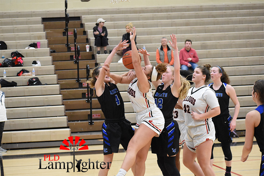 Elise Ellison-Coons, #5, gets hit in the face with the basketball while trying to get the rebound.