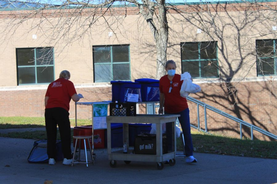 Mrs. Rhonda Lawson and Ms. Charlotte Buckner taking the last meal bag from one of five boxes.