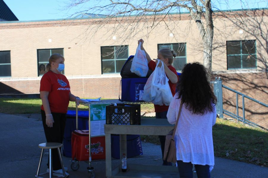 Dunbar's cafeteria staff giving meal bags to a Dunbar parent for her two children.