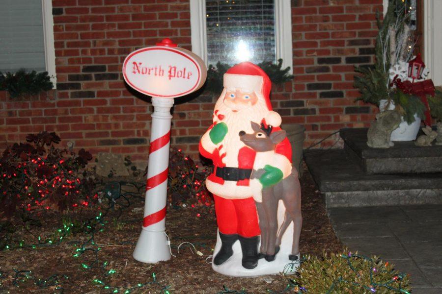 Santa decoration hugging a reindeer in a neighbors front yard.