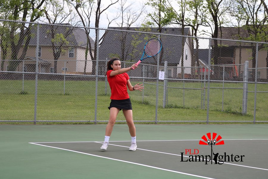 Freshman Erika Reid hits the ball to her opponent with a forehand return.