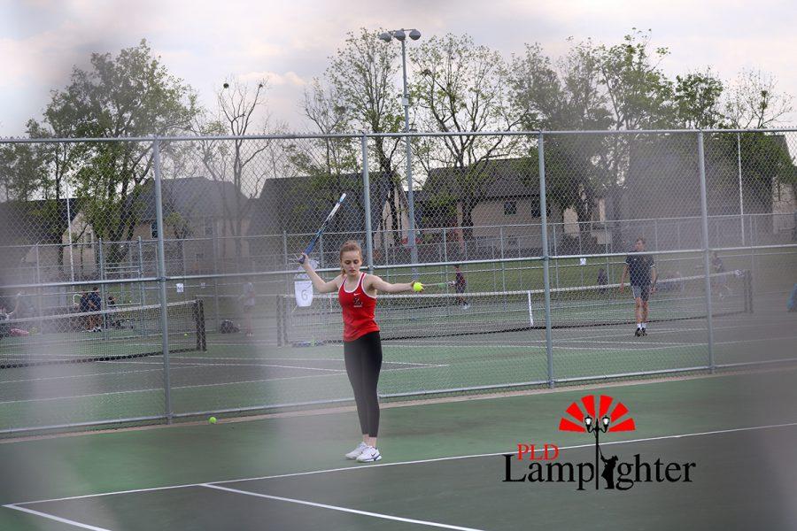 Senior Bella Burns prepares to toss the ball for her serve.